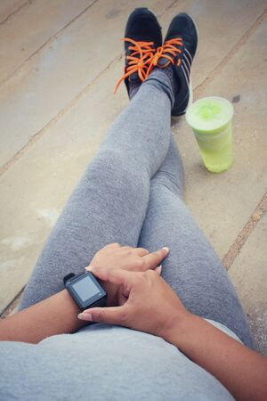 girl with a wristwatch: Woman running shoe and smartwatch with green vegetable smoothie. Stock Photo