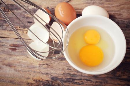 Los huevos en un cuenco con un batidor Foto de archivo - 42372485