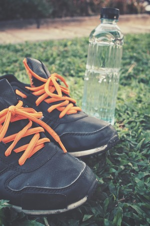 water shoes: Sport shoes with water drink on green grass