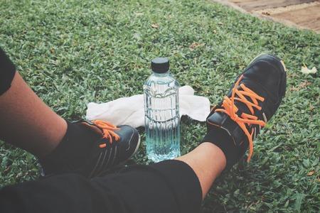 tomando agua: Autofoto de zapatos y una toalla con la bebida del agua en la hierba verde
