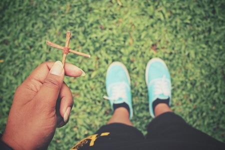 orando: Manos de rogación con la cruz
