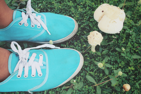 dirty feet: Selfie of sneakers with mushrooms on grass Stock Photo