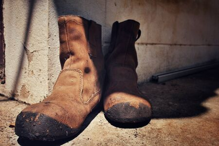 dirty feet: Old boots with shadow Stock Photo