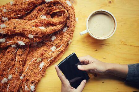 mujer tomando cafe: Café de la bebida de la mujer con el teléfono inteligente y euroconector