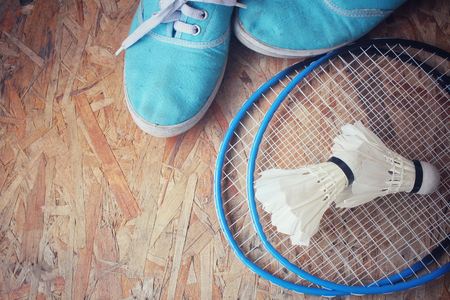 badminton: Sneakers with shuttlecocks and badminton racket.