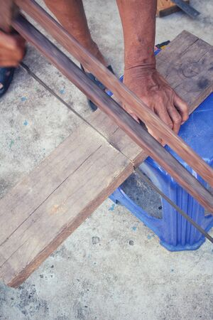 foremen: Man cutting the wood