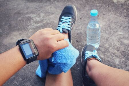 sport shoe: Selfie of smartwatch and sport shoes with water drink on green grass