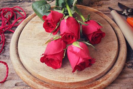 mujer con rosas: Haciendo ramo de flores con rosas rojas