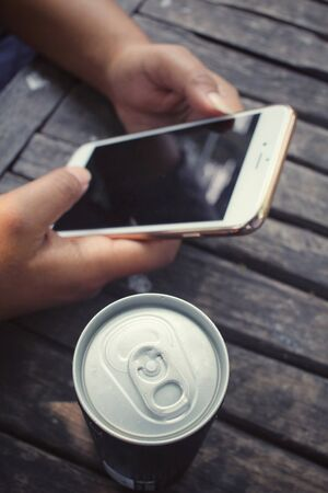 aluminum can: Woman using smart phone with aluminum can Stock Photo