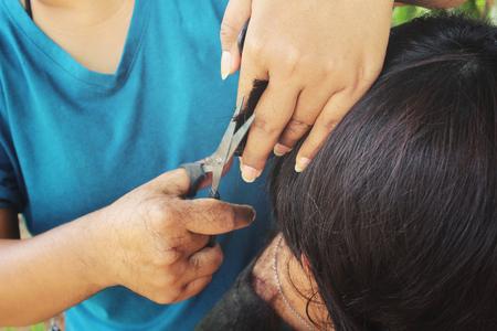 cutting hair: Hairdresser cutting hair with scissors