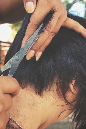 hairdresser cutting hair: Hairdresser cutting hair with scissors