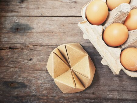 Eggs in box with paper fortune teller Stock Photo