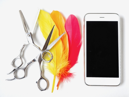 Hair cutting shears with colorful feathers  and smart phone Stock Photo