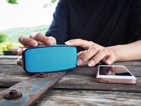 Vrouw die draadloze spreker met slimme telefoon met behulp van Stockfoto