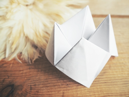 Paper fortune teller with white feathers