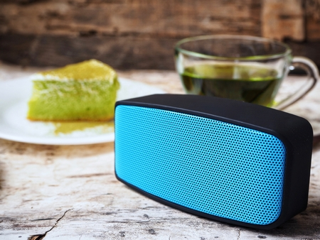 electronic music: Bluetooth speaker and green tea with cake