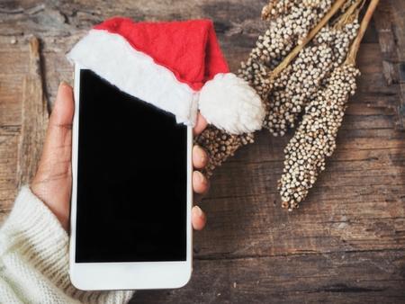 Slimme telefoon met kerstmuts Stockfoto