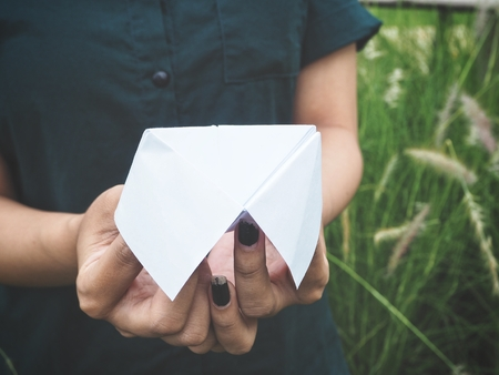 Paper fortune teller on hands with grass flowers