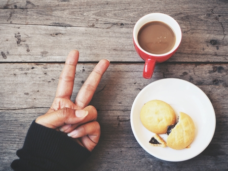 Crossed fingers with coffee cup and cookie