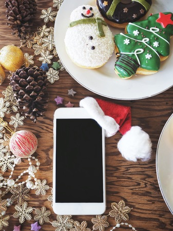Smart phone with christmas hat and donuts