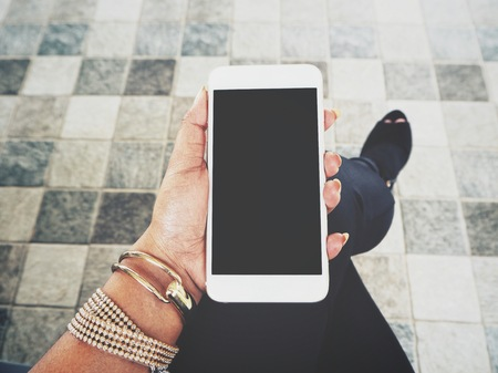 Selfie of woman using smart phone on hand and shoes