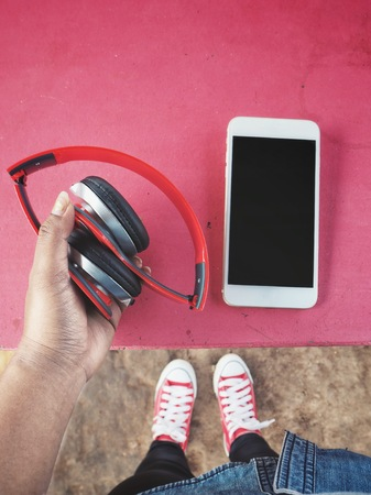 Selfie of headphones with smartphone and sneakers 스톡 콘텐츠