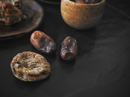 Fig and date fruits on black background