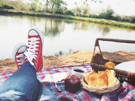Selfie of picnic breakfast and sneakers at lake
