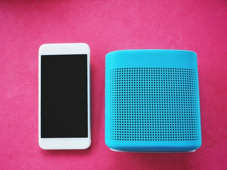 Blue speaker and smart phone on pink background