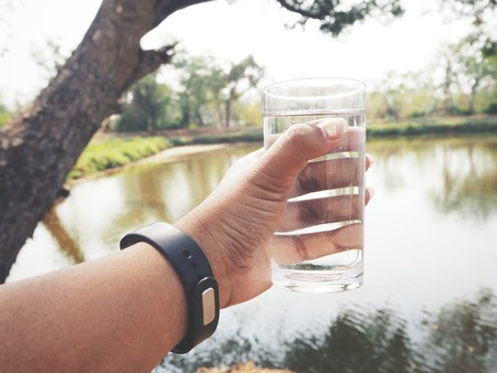 Selfie of water drink with glass on hand 스톡 콘텐츠