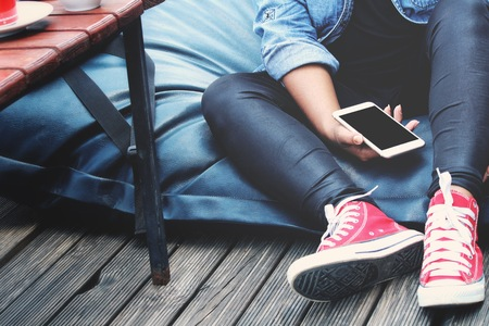 Woman using smart phone on hand and red sneakers lifestyle so cool