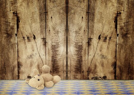 pine boughs: Old Gold colored Teddy Bear lying on a striped plank rustic background.