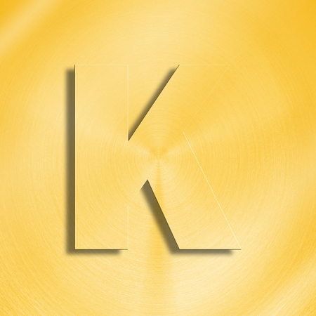 oblique line: 3d rendering of the letter K in gold metal on a golden isolated background. Stock Photo