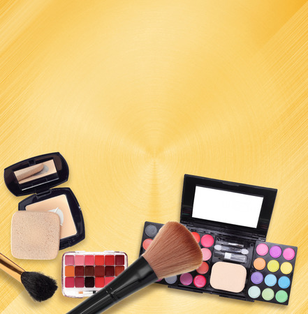 Various makeup products on a gold background.