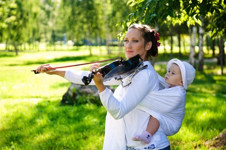 sling: Play on a violin with the child Stock Photo