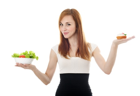 Young businesswoman choice lettuce salad or cake. Isolated on the white background photo
