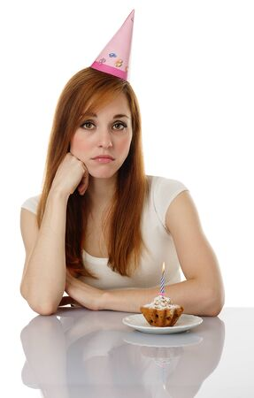 Sad girl with birthday cake isolated on white background photo