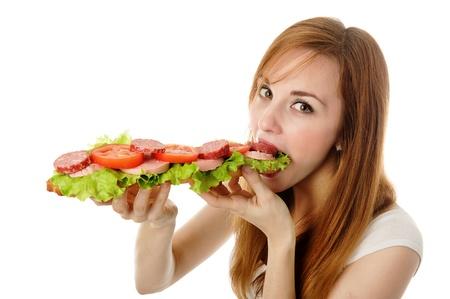 gula: mujer joven comer comida r�pida. aislado en blanco Foto de archivo