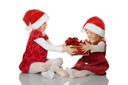 dar un regalo: La chica le da a la hermana un regalo. aislados en el blanco
