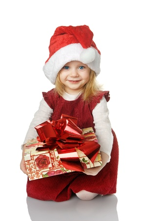 The girl in Santa hat with a gift. isolated on the white photo