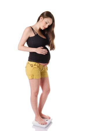 Attractive pregnant female using a scale. isolated on white background photo
