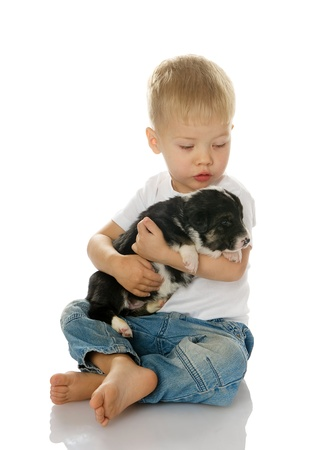 Happy kid boy bonding his puppy dog isolated on white background