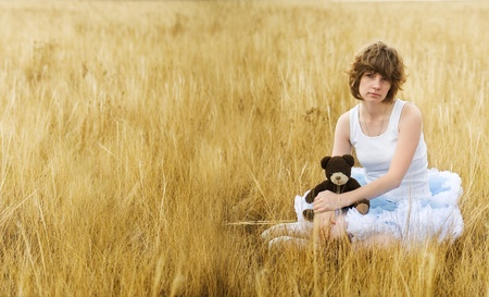myst: The sad girl in the field with a bear in a hand  Stock Photo