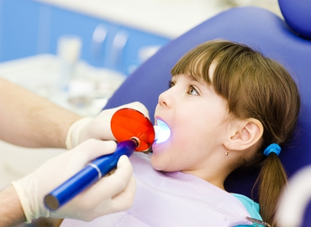 girl open mouth: little girl with open mouth receiving dental filling drying procedure