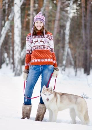 ropa de invierno: Chica con su perro lindo en el bosque de invierno