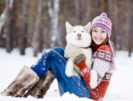 beautiful girl in winter forest with dog Stock Photo