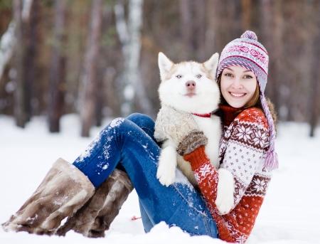jugar: hermosa niña en el bosque de invierno con el perro