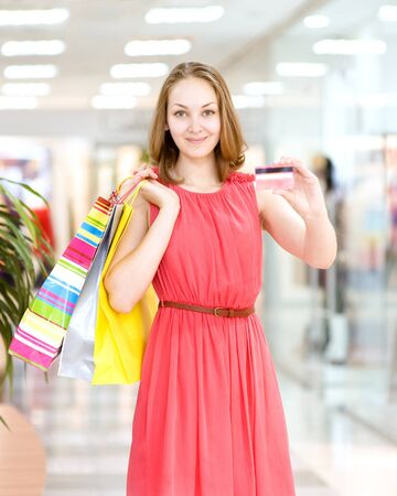 Beautiful young woman with shopping bags and credit card photo