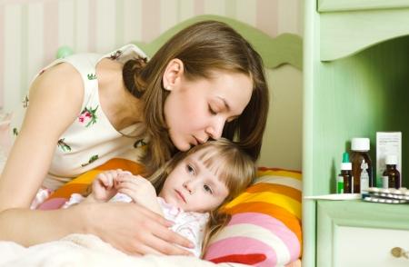 sick child: mother kisses the sick child