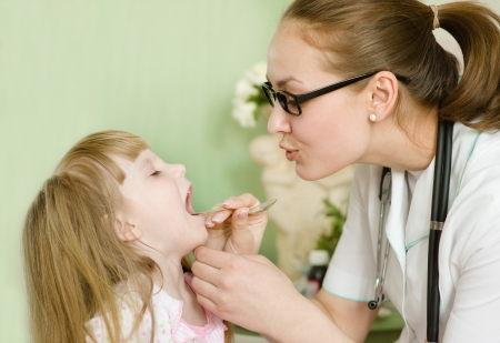 Pediatrician examining little girl s throat photo
